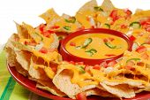 stock photo of jalapeno  - Plate of fresh nachos with a spicy jalapeno cheese sauce - JPG