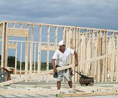 foto of lumber  - Framer is moving a large piece of unwieldy lumber on the framing jobsite of a new house - JPG