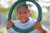 stock photo of swingset  - Little Girl Having Fun Playing at the Playground - JPG