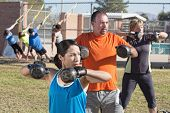 pic of boot camp  - Men and women in boot camp fitness class outdoors - JPG