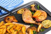 Homemade roasted chicken drumsticks with fried potatoes and vegetables on pan, isolated on white