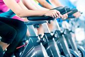 stock photo of cardio  - Group of four people spinning in the gym - JPG