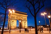 pic of charles de gaulle  - The Arc de Triomphe in Paris France at twilight with traffic light trails - JPG