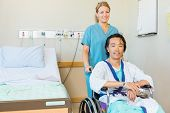 Portrait of mature patient sitting on wheelchair while nurse assisting him in hospital