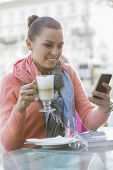 Young woman having coffee while using cell phone at sidewalk cafe