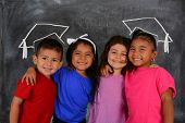 stock photo of chalkboard  - Young children at school standing at the chalkboard - JPG