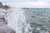 pic of gushing  - Gushing surf of a wave smashing against seaport at Thessaloniki Greece - JPG