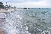 foto of gushing  - Gushing surf of a wave smashing against seaport at Thessaloniki Greece - JPG
