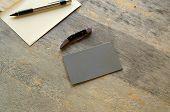 stock photo of manila paper  - A pencil paper knife and grey card are seen on an old wooden table - JPG