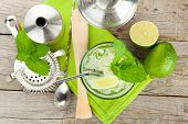 stock photo of mojito  - Fresh mojito cocktail and bar utensils on wooden table - JPG
