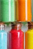 foto of pigment  - Bottles with colorful dry pigments on wooden background - JPG