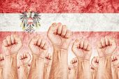 foto of labourer  - Austria Labour movement workers union strike concept with male fists raised in the air fighting for their rights Austrian national flag in out of focus background - JPG