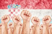 picture of labourer  - Croatia Labour movement workers union strike concept with male fists raised in the air fighting for their rights Croatian national flag in out of focus background - JPG