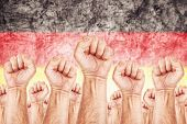 foto of labourer  - Germany Labour movement workers union strike concept with male fists raised in the air fighting for their rights German national flag in out of focus background - JPG
