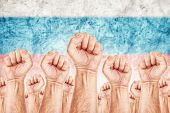 image of labourer  - Russia Labour movement workers union strike concept with male fists raised in the air fighting for their rights Russian national flag in out of focus background - JPG