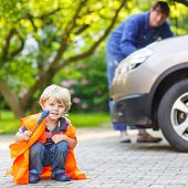 stock photo of breakdown  - Funny child in orange safety vest during his father repairing family car on background - JPG