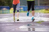 image of rainy weather  - Young couple jogging on asphalt in rainy weather - JPG