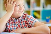 stock photo of schoolboys  - Cute elementary schoolboy looking aside with smile - JPG