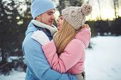 image of amor  - Amorous couple in embrace looking at one another in park - JPG