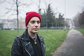 foto of anarchists  - Punk guy with beanie posing in a city park - JPG