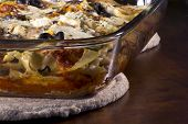 stock photo of artichoke hearts  - Homade vegetarian lasagna casserole topped with sliced mushrooms olives and artichoke hearts - JPG
