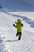 stock photo of snow-slide  - Girl in green running in the snow with slides and laughs - JPG