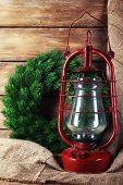 foto of kerosene lamp  - Kerosene lamp with wreath on wooden planks background - JPG