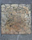 stock photo of porphyry  - heavily damaged tile of orange white marble - JPG