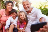 image of grandparent child  - Grandparents With Grandchildren In Garden Taking Selfie - JPG