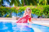picture of swimming pool family  - Beautiful little girl cute toddler with curly hair wearing a red summer dress sitting at a swimming pool drinking water melon juice with fresh fruit having fun during family vacation in a tropical resort  - JPG