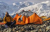 stock photo of shan  - Adventurous hiker camping near Engilchek glacier in scenic Tian Shan mountain range in Kyrgyzstan - JPG