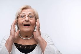 stock photo of crazy face  - Grandmother surprised. Closeup of a surprised senior woman holding hands by her face isolated over white background ** Note: Soft Focus at 100%, best at smaller sizes - JPG