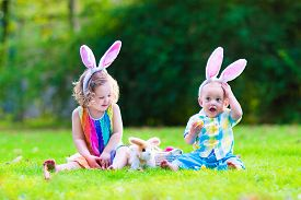 picture of little sister  - Two little children cute curly toddler girl and funny baby boy wearing bunny ears having fun at Easter egg hunt playing with basket and toy rabbit in a sunny spring garden
