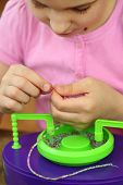 stock photo of beads  - Girl bowing head collects shallow color beads - JPG
