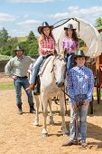 stock photo of wagon  - cowboy family of four with wagon and horse - JPG