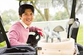 image of buggy  - Happy golfer driving his golf buggy smiling at camera at the golf course - JPG