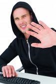 stock photo of frown  - Frowning hacker gesturing and looking at camera on white background - JPG