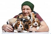 foto of puppy beagle  - The happy man and big group of a beagle puppies on white background - JPG