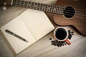 stock photo of ukulele  - Cup of coffee with ukulele and notebook on wooden table Vintage style - JPG