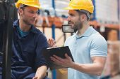 pic of warehouse  - Smiling warehouse workers talking together in warehouse - JPG