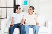 stock photo of grown up  - Asian senior father and adult son having conversation at home - JPG