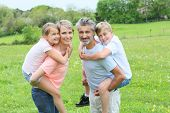 picture of piggyback ride  - Parents giving piggyback ride to kids in countryside - JPG