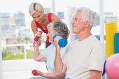 picture of senior class  - Senior man lifting dumbbells while trainer assisting woman in background at gym - JPG