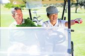 image of buggy  - Golfing friends driving in their golf buggy at the golf course - JPG