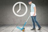 foto of trolley  - Confident delivery man pushing empty trolley against grey room - JPG