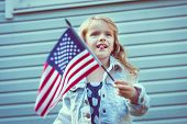 pic of long tongue  - Funny little girl with long curly blond hair putting out her tongue and waving american flag - JPG