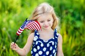 stock photo of pretty girl  - Pretty pensive little girl with long curly blond hair holding an american flag and smiling on sunny day in summer park - JPG