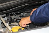 stock photo of car repair shop  - auto mechanic is working on engine in car repair shop  - JPG