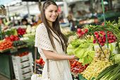 foto of farmers market vegetables  - Young woman on the market shopping for fruits and vegetables