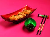 image of deep  - traditional Vietnam deep fried shrimp and pork rolls in breadcrumbs served on a pink background - JPG
